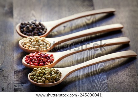 Mixed green, red, white and black peppercorns in a wooden spoon, shallow depth of field - stock photo