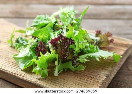 Mixed green salad on wooden cutting board, closeup - stock photo