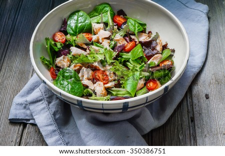 Mixed Green Salad with Grilled Salmon and Quinoa on Wood Background/ Selective Focus - stock photo