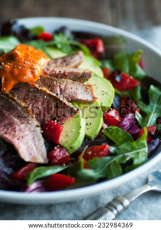 Mixed green salad with roast beef and smoked paprika aioli - stock photo
