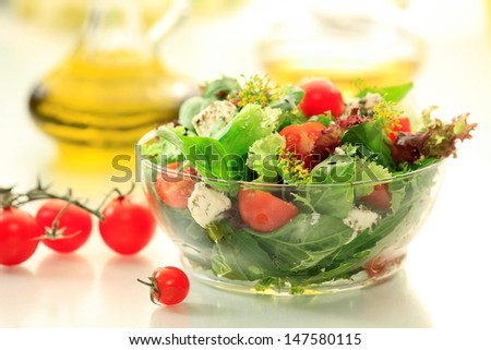Mixed green salad with  Rocket / rukola, Lettuce, Spinach, Feta  cheese, Lollo rosso, Lollo Bionda  and fresh Cherry Tomatoes  in a  clear glass bowl - stock photo
