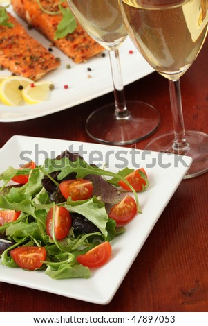 Mixed greens with cherry tomatoes. Wine and smoked salmon in background