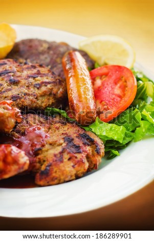 Mixed grill with red bbq sauce on a plate (selective focus)  - stock photo