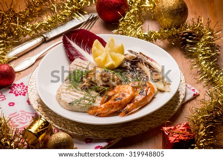 mixed grilled fish with red chicory over christmas table - stock photo