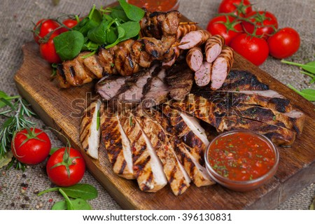 Mixed grilled meat platter. Assorted delicious grilled meat with vegetable. Mixed grilled meat with pepper sauce and vegetables. - stock photo