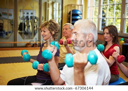 Mixed group doing dumbbell exercises in a gym - stock photo