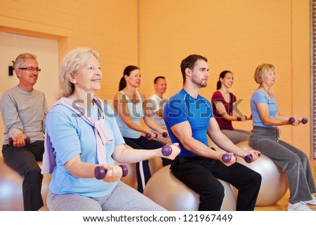 Mixed group doing dumbbell training in a health club - stock photo