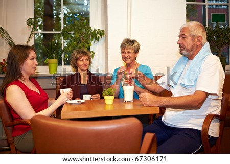 Mixed group drinking coffee in a gym - stock photo