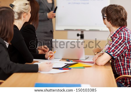 mixed group listening to woman at flipchart - stock photo