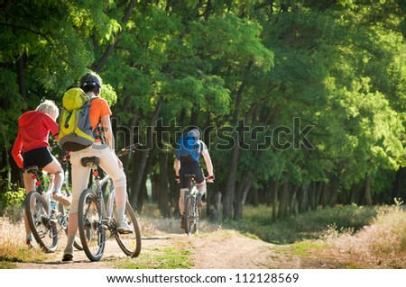 mixed group of cyclists biking summer day - stock photo
