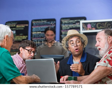 Mixed group of four mature men talking in cafe - stock photo
