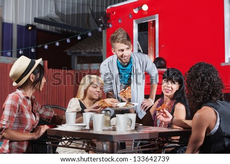 Mixed group of friends talking and eating pizza - stock photo
