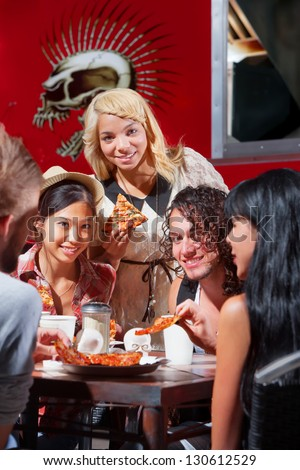 Mixed group of happy people eating pizza outside - stock photo
