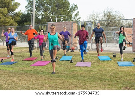 Mixed group of mature adults in boot camp exercise - stock photo