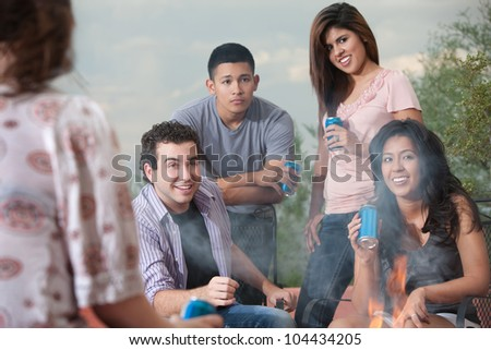 Mixed group of young people drinking soda at a campfire - stock photo