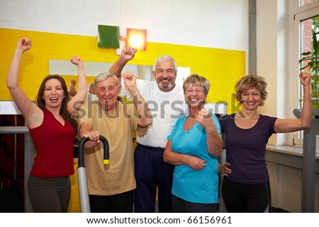 Mixed group with elderly people in a gym cheering - stock photo