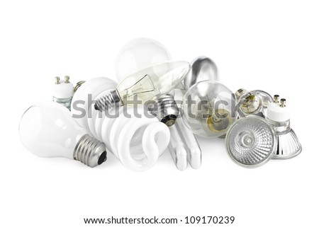 Mixed heap of light bulbs with filament bulbs and energy salving lamps on white - stock photo