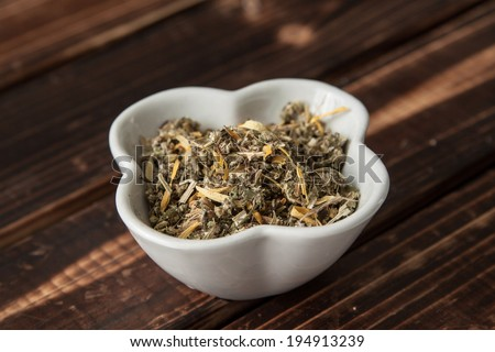 mixed herb tea in a bowl , wood background