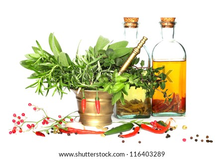 Mixed herbs of sage, rosemary, basil with red hot pepper in mortar with pestle  bottle of oil on white background - stock photo