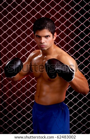 Mixed martial artist posed in front of chain link - stock photo