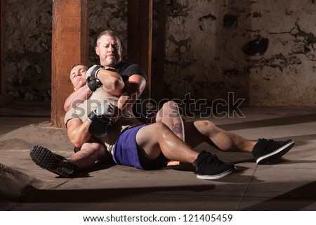 Mixed martial artist with opponent in submission choke hold - stock photo