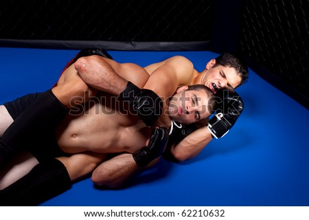 Mixed martial artists fighting - ground fighting - stock photo