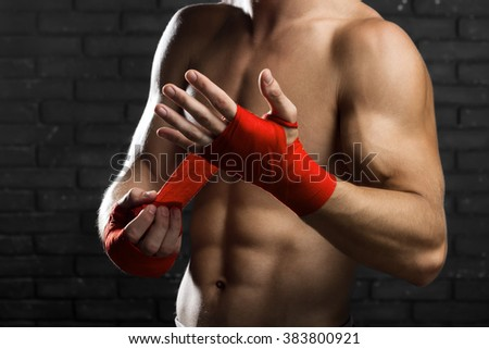 Mixed Martial Arts Fighter Preparing Bandages For Training - stock photo
