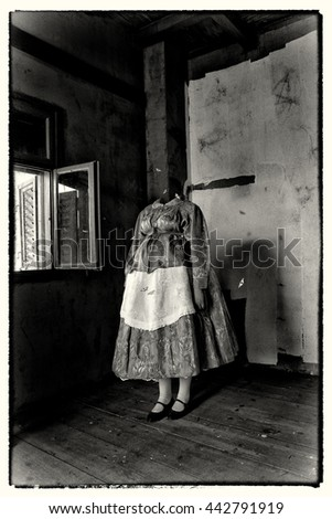Mixed media artwork. A woman without a head, wearing folk costume, standing in the somber room, surrounded by butterflies. Additional post processing to look like an old photo. - stock photo