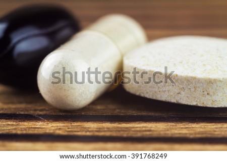 Mixed natural food supplement pills, vitamin c, carotene, glucosamine capsules on wooden table, macro image, selective focus - stock photo