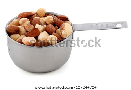 Mixed nuts - almonds, hazelnuts and brazil nuts - presented in an American metal cup measure, isolated on a white background