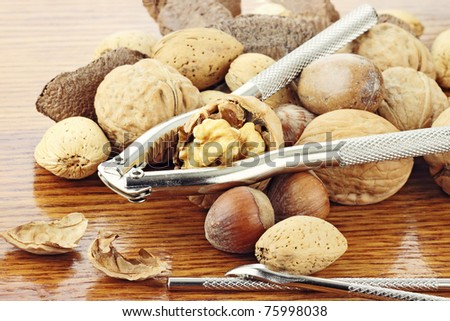 Mixed nuts and a nut cracker on a wooden table with reflection in wood. Shallow depth of field.