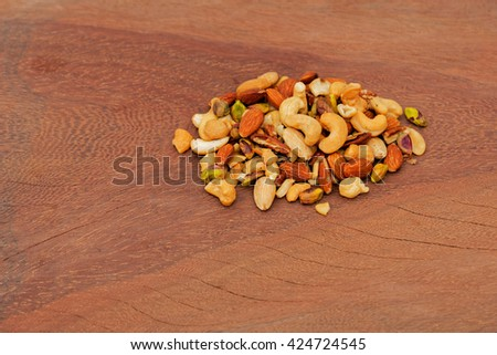 Mixed nuts heap on a wooden board. Cashews, almonds, pistachios, pecans. - stock photo