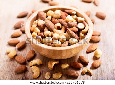 mixed nuts in a bowl on wooden table.