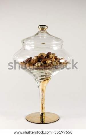 Mixed nuts in a glass container on a white background.