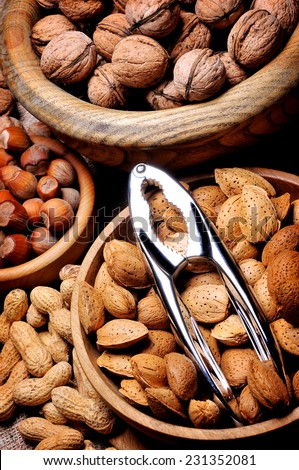 Mixed nuts in bowl with nut cracker - stock photo