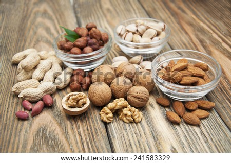 Mixed nuts  in glass bowls on a wooden background  - stock photo