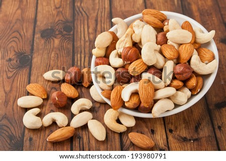 mixed nuts in white bowl - stock photo