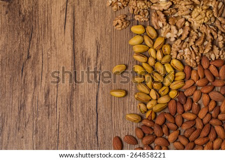 Mixed nuts on wooden background - Nuts frame top view - stock photo