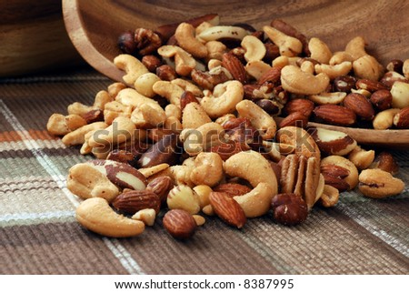 Mixed nuts spilling out of a wooden bowl onto color coordinated placemat.  Macro still-life with shallow dof - stock photo