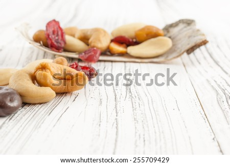 Mixed of dried fruits and nuts with chocolate on white wooden background - stock photo