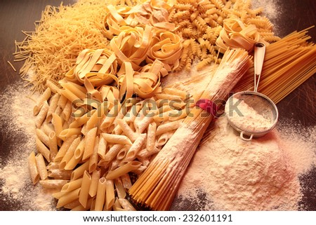 Mixed of shapes and types of pasta with flour - stock photo