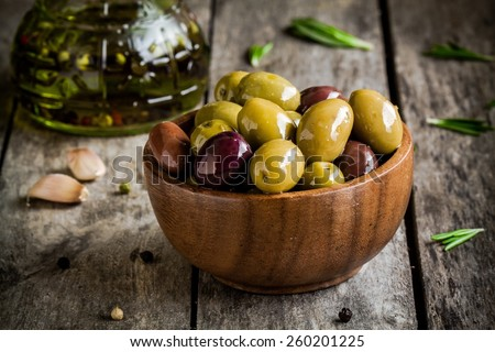mixed olives in a wooden bowl with rosemary, olive oil and garlic on rustic table - stock photo