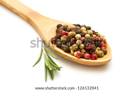 Mixed pepper in wooden spoon with rosemary isolated on white background