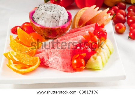 mixed plate of fresh fruits,pitaya or dragon fruit with watermelon, orange,apple and cherry tomatoes - stock photo