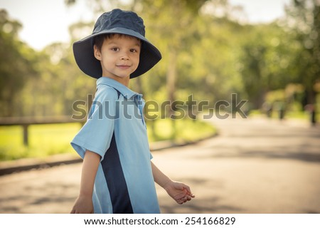 Mixed race Asian Caucasian boy confidently leaves home on his first day of school. Wearing uniform and sun hat. Walking down his suburban street in the summer sun - stock photo