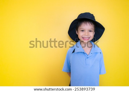 Mixed race Asian Caucasian boy on his first day back to school. Standing in front of a cheerful yellow background with copy space. - stock photo