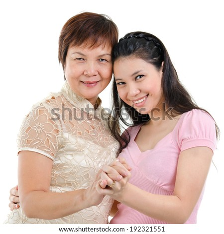 Mixed race Asian family portrait. Elderly mother and adult daughter holding hands bonding isolated on white background. - stock photo