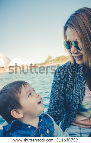 Mixed race Asian Thai Australian family traveling as tourists together and playing while visiting the Sydney Opera House in Sydney, Australia. Filtered and color shift effects - stock photo