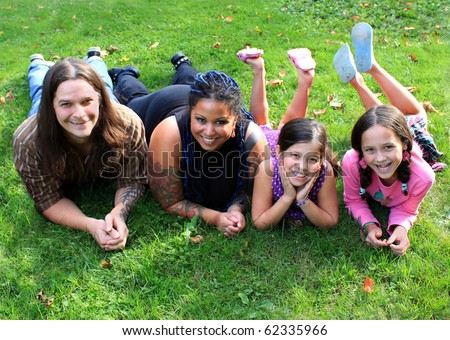 Mixed race beautiful ethnic family with parents and two children laying on the grass - stock photo