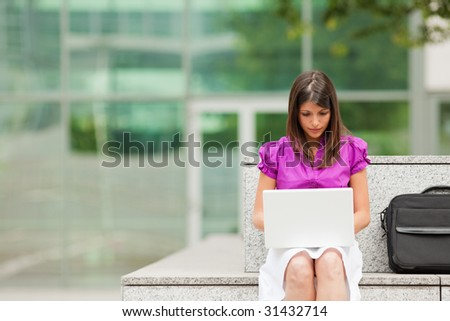 mixed-race business woman using laptop computer outdoors. Copy space - stock photo